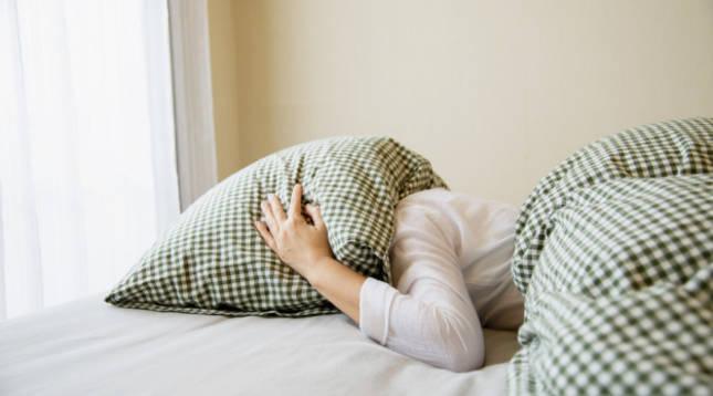 Una persona insomne se tapa con una almohada