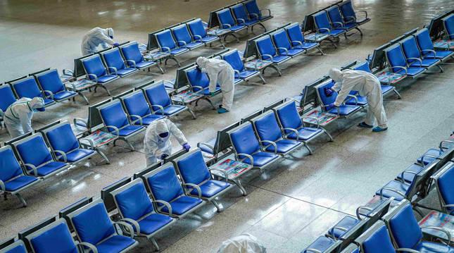 Varios trabajadores protegidos desinfectan los asientos de la estación de tren de Wuhan.
