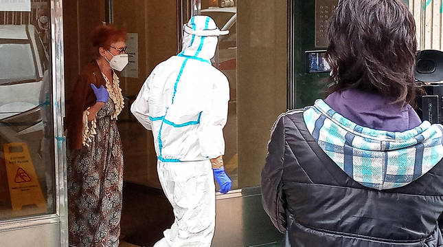 Una de las personas infectadas sale del edificio para ser trasladada a un centro sanitario de Santander.