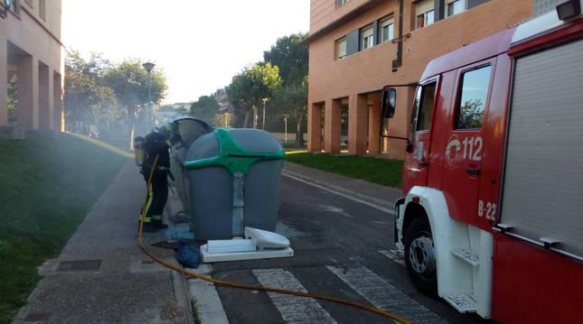 Foto del momento en el que los bomberos sofocan el fuego del contenedor.