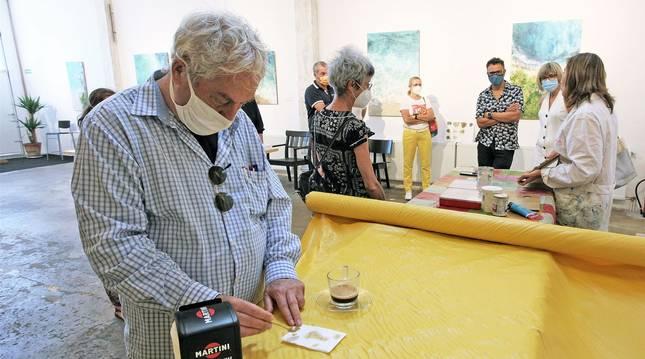 Juan Osés y Susana Arancón, con los asistentes a una visita guiada a las exposiciones. Juan Oses dibujó sobre manchas de café y la artista tudelana  explicó su pintura matérica.
