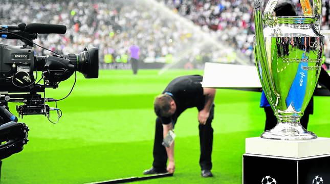 Un cámara de televisión filma la copa de la Champions antes de arrancar la final que conquistó el Real Madrid.