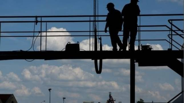 Imagen de archivo de dos trabajadores en un andamio.