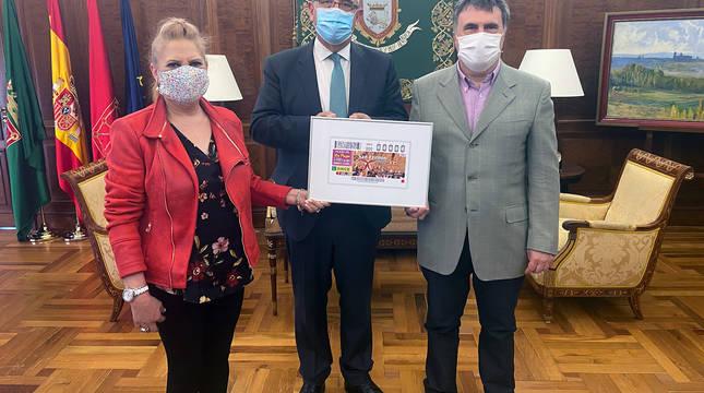 Valentín Fortún, delegado de la ONCE en Navarra, Pilar Herrero, presidenta del consejo territorial de la ONCE, y Enrique Maya, alcalde dePamplona, posan con el cupón del 7 de julio.