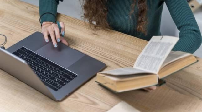 Una joven estudia idiomas con ayuda de un diccionario