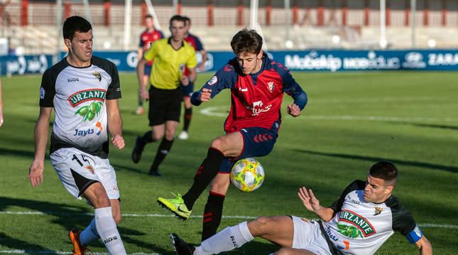 El rojillo Aimar Oroz trata de zafarse de Unai Zamorano y Lalaguna, en el derbi de esta temporada.