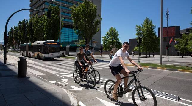 Foto de tres ciclistas recorriendo el nuevo carril, frente a la plaza de Baluarte.