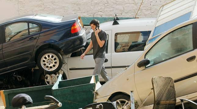 Foto de una persona llamando por teléfono en el escenario de caos que dejaron las inundaciones en Tafalla.