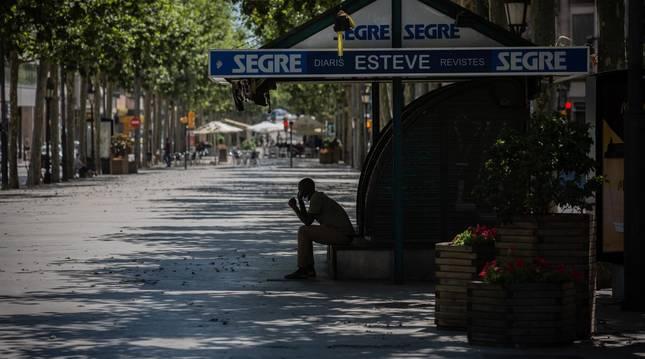 Foto de un hombre descansando a la sombra en una calle de Lleida, capital de la comarca del Segrià, en Lleida, Cataluña.