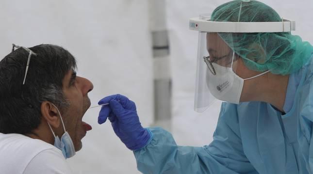 Una sanitaria le realiza un frotis bucal a un vecino de Ordizia en una de las carpas instaladas en el parque Barrena por el Ayuntamiento de Ordizia para realizar test ante el posible brote de COVID-19 detectado en la localidad guipuzcoana