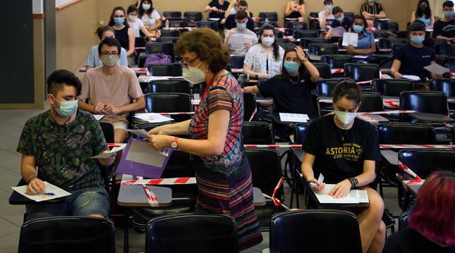 Foto de una profesora repartiendo exámenes de la EvAU en la Universidad de Barcelona.