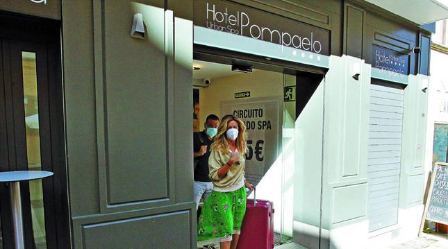 Foto de dos turistas abandonando un hotel en el centro de Pamplona.