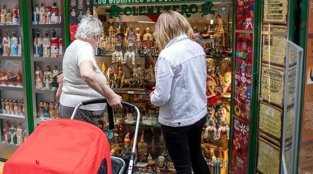 Foto de unos clientes observando el escaparate de la tienda de souvenirs Olentzero, situada en la calle Estafeta.