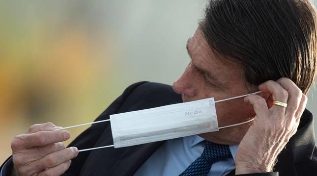 Jair Bolsonaro se pone una mascarilla durante una ceremonia oficial, el 9 de junio de 2020, en el Palacio do Alvorada, en Brasilia (Brasil).