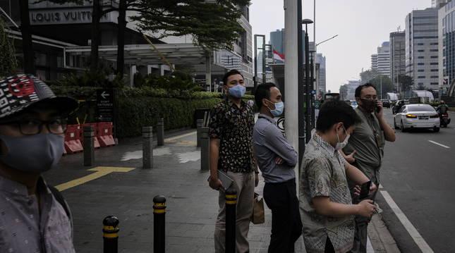 Varias personas paradas en un paso en Yakarta, Indonesia.