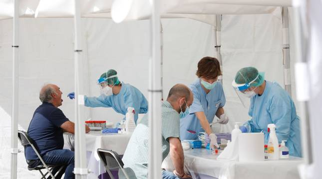Foto de dos vecinos de Ordizia (Guipúzcoa) haciéndose las pruebas de coronavirus este miércoles en las carpas instaladas en la localidad.