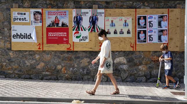 Una mujer camina en Ordizia delante de unos carteles electorales.