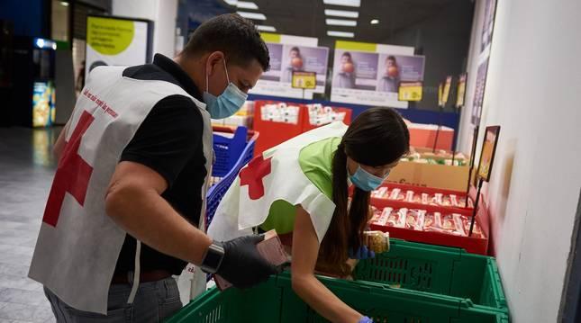 Foto de dos voluntarios de Cruz Roja, en la campaña de reparto de alimentos.