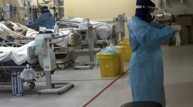 Una sanitaria se prepara para atender a un grupo de pacientes afectados por la COVID-19 en la Unidad de Cuidados Intensivos (UCI) del Hospital Clínico de la Universidad de Chile en Santiago.