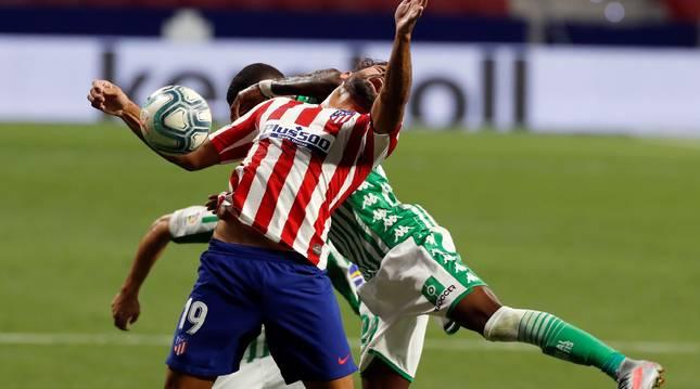 El delantero del Atlético de Madrid Diego Costa (d) salta a por un balón con Emerson, del Betis.