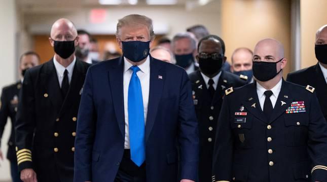 El presidente de los Estados Unidos, Donald J. Trump (C), usa una máscara a su llegada para visitar a militares heridos y a trabajadores de atención médica de coronavirus de primera línea en el Centro Médico Nacional Militar Walter Reed en Bethesda.