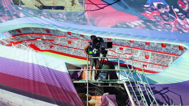 Un cámara de televisión, durante el Osasuna-Getafe, situado en una de las gradas de El Sadar que están tapadas actualmente con lonas que proyectan el estadio reformado y ampliado.