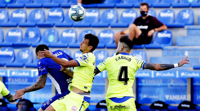 El delantero del Alavés Joselu pugna por un balón aéreo con los jugadores del Getafe Maksimovic y Cabaco.