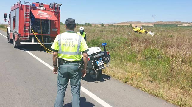 Un agente de la Guardia Civil en el lugar del suceso con el automóvil accidentado en la derecha de la imagen