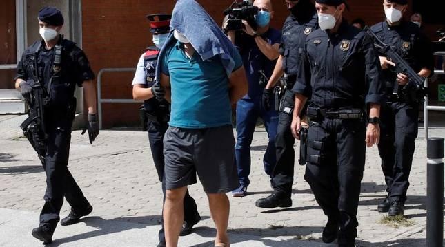 Mossos d'esquadra custodian a uno de los detenidos en la operación contra el terrorismo yihadista.