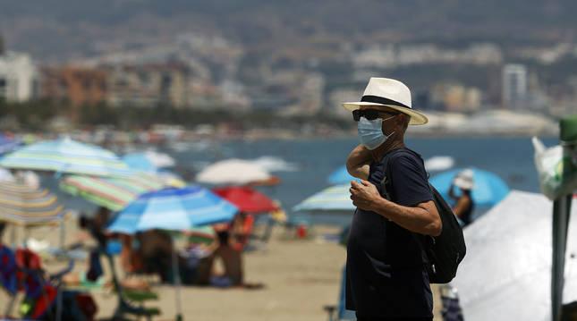 Una persona cubierta con una mascarilla en una playa de Málaga este miércoles, primer día de uso obligatorio de la protección.