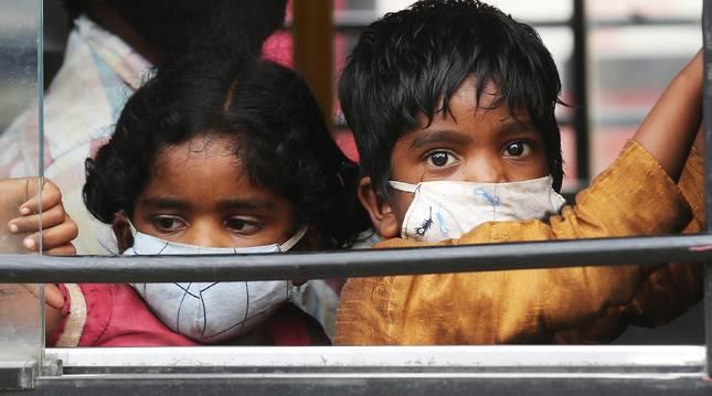 Foto de dos niños indios con mascarilla en el interior de un autobús este martes en Bangalore, India.