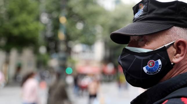 Foto de un ertzaina con doble mascarilla en Bilbao.