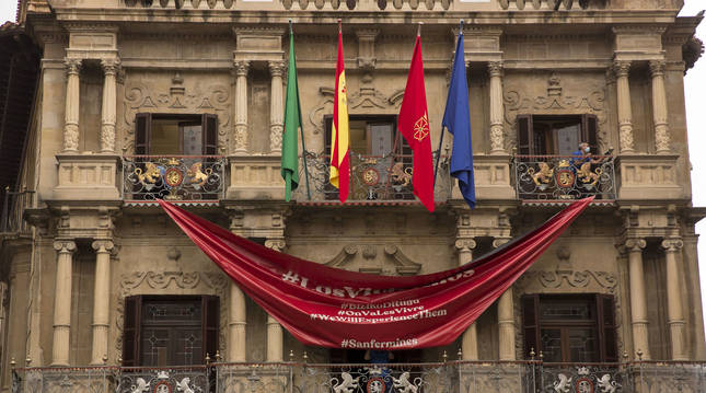 Foto de la retirada de la lona que simulaba un gran pañuelo rojo en la fachada del Ayuntamiento de Pamplona.
