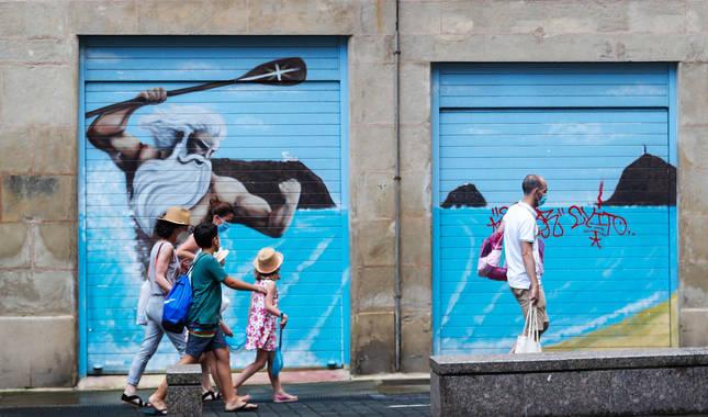 Una familia camina por las calles del casco viejo de San Sebastián cubiertos con mascarillas.