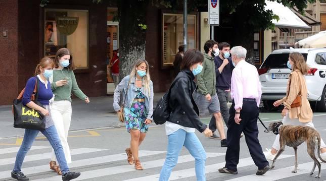 Personas que están cruzando un paso de peatones en el centro de Pamplona, todos con mascarilla.