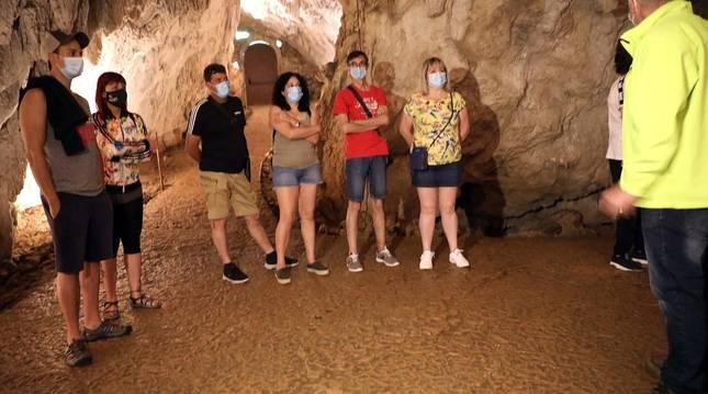 Foto de un grupo de visitantes atiende las explicaciones del guía en las cuevas de Urdax.
