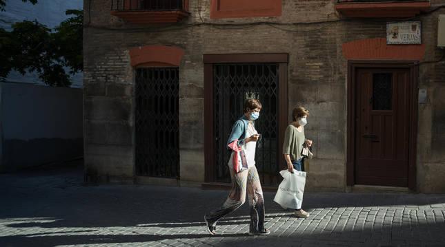 Dos mujeres con mascarilla por la calle Verjas de Tudela.