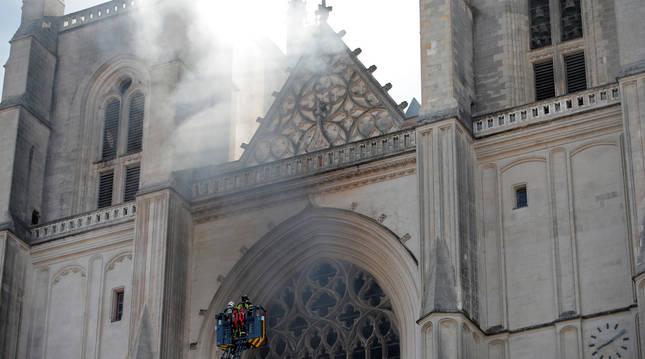 Efectivos de bomberos intentan apagar el fuego que sale del rosetón central de la catedral de Nantes.