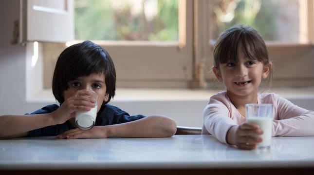 Dos niños bebiendo un vaso de leche.