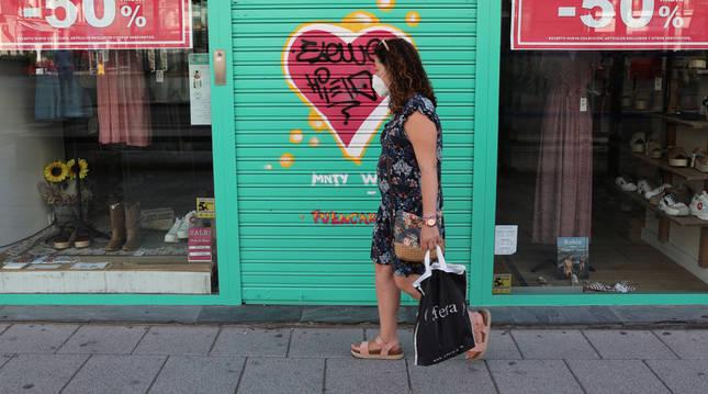Una mujer protegida por una mascarilla pasa por delante de un negocio cerrado en Madrid.