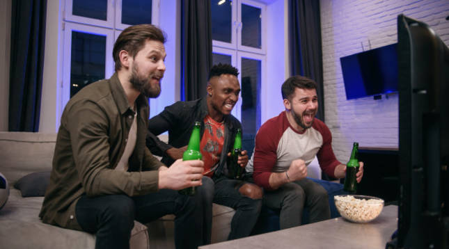 Tres amigos siguen un partido de la NBA por televisión