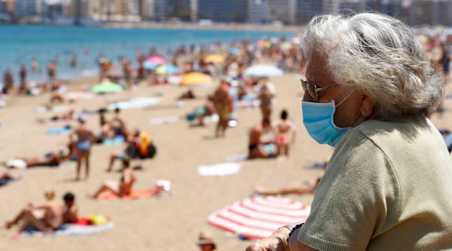 Foto de una mujer con mascarilla, en una playa de Las Palmas de Gran Canaria.