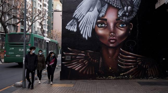 Un grupo de jóvenes con mascarillas, durante la cuarentena obligatoria decretada para frenar el avance de la COVID-19, este jueves, en Santiago (Chile).
