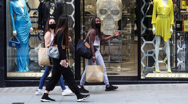 Tres jóvenes protegidas con mascarillas pasean ante un establecimiento de la calle New Bond en Londres.