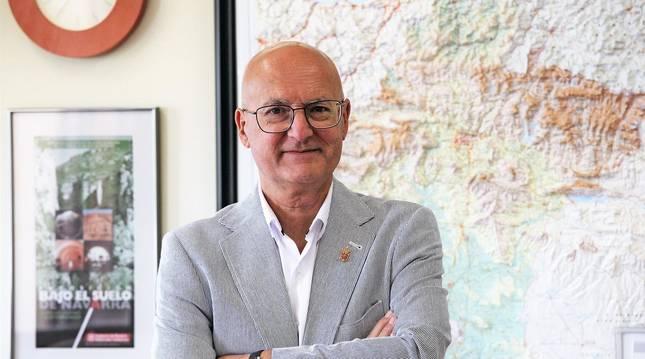Foto del consejero Bernardo Ciriza posa en su despacho del departamento, delante de un mapa de Navarra en relieve.