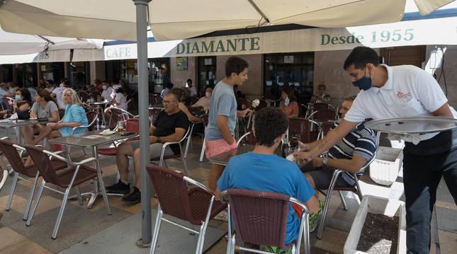 Un camarero sirve a unos clientes en la terraza del bar Diamante de la plaza de los Fueros.