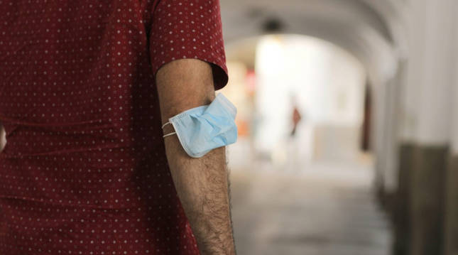 Un hombre camina con una mascarilla en el brazo.