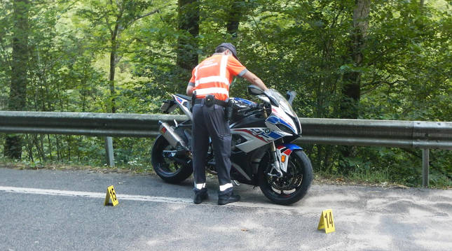 Un agente de la Policía Foral sostiene la motocicleta tras el accidente en Valcarlos.