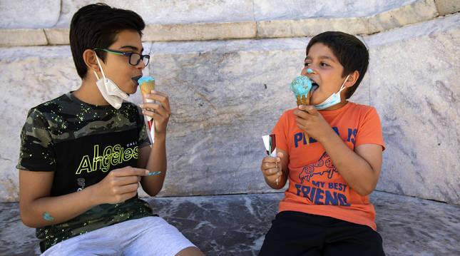 Dos niños disfrutan de un apetecible helado de pitufo también conocido como Blue Ice con virutas de colorines espolvoreadas por encima.