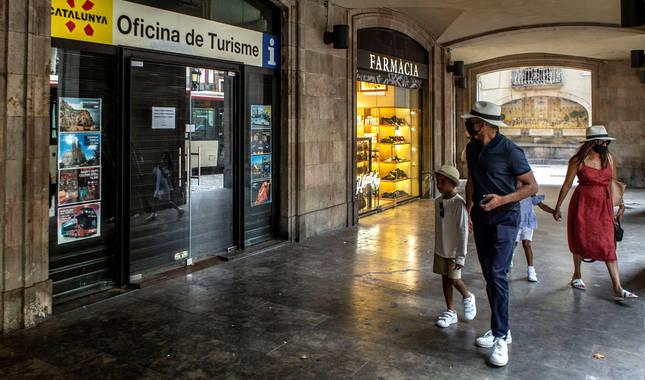 Una familia de turismo se da la vuelta ante una oficina de información cerrada en Barcelona